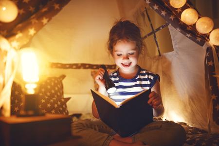 Glückliches Kind Mädchen lachen und lesen Buch in einem dunklen Zelt auf einem Sofa zu Hause Standard-Bild - 94882449