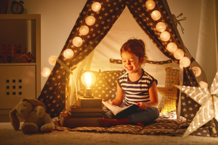 happy child girl laughing and reading book in dark in a tent at home
