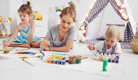 childrens creativity. mother and children draw paints in the playroom  Stock Photo