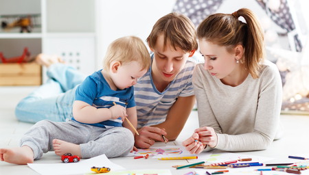 어린이 창의력. 행복한 가족 어머니 아버지와 아기 아들이 함께 그려.
