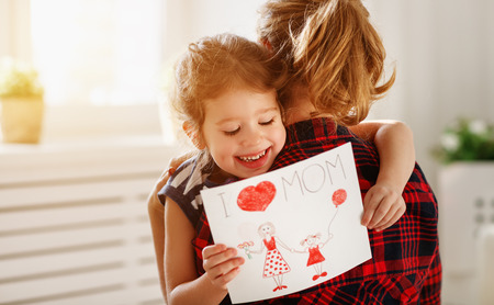Happy mothers day! Daughter gives her mother an postcard and hugs  Stock Photo