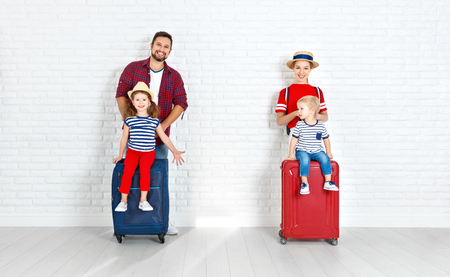 Konzeptreisen und Tourismus. glückliche Familie mit Koffern nahe leerer Wand Standard-Bild