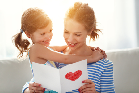 Happy mothers day! Child daughter congratulates moms and gives her a postcard    Banco de Imagens