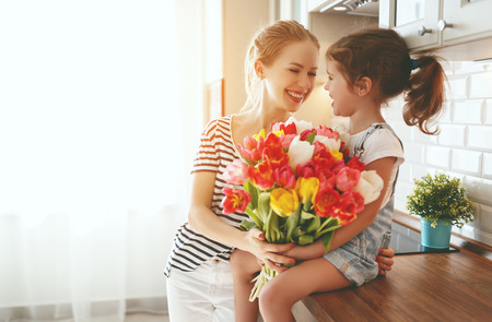happy mother's day! child daughter congratulates mother and gives a bouquet of flowers to tulips Banque d'images