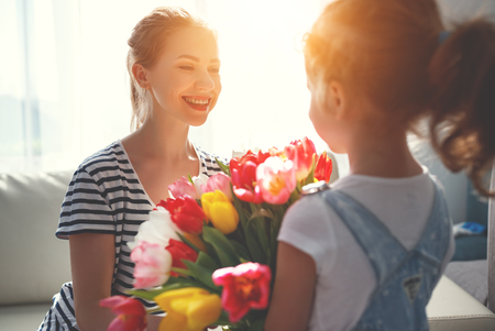 happy mother's day! child daughter congratulates mother and gives a bouquet of flowers to tulips Banco de Imagens
