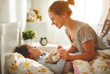 morning awakening. mother wakes her daughter in bed in morning
