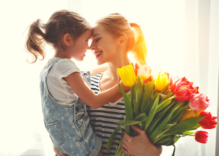 happy mothers day! child daughter congratulates mother and gives a bouquet of flowers to tulips  Banco de Imagens