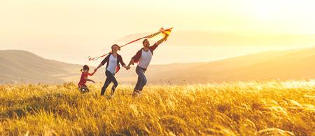 Gelukkige familievader, moeder en kinddochter lanceren een vlieger op aard bij zonsondergang Stockfoto