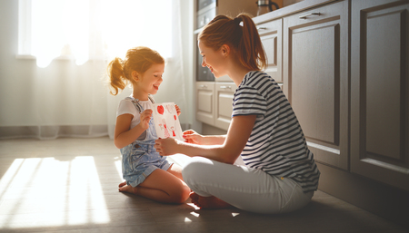 happy mothers day! child daughter congratulates her mother and on  floor in kitchen read postcard  Banco de Imagens