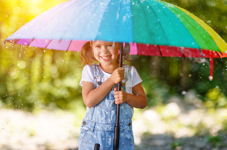 Happy child girl laughs and plays under the summer rain with an umbrella  Stock Photo