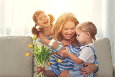 Happy mother's day! Children congratulates moms and gives her a gift and flowers tulips Banco de Imagens