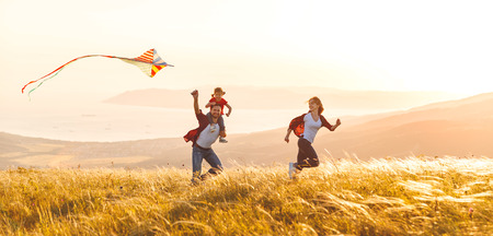 Happy family father,  mother and child daughter launch a kite on nature at sunset 스톡 콘텐츠