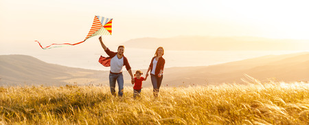 Happy family father,  mother and child daughter launch a kite on nature at sunset