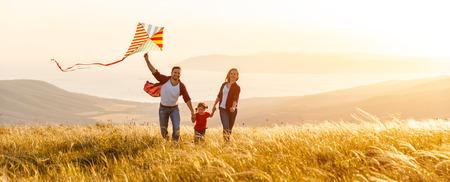 Glückliche Familienvater-, Mutter- und Kindertochter starten einen Drachen auf Natur bei Sonnenuntergang