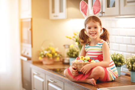 Happy easter! funny child girl with rabbit ears and a basket  of eggs at home in kitchen