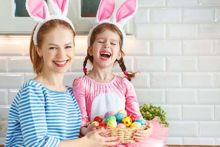 Felices Pascuas! madre de familia e hija con orejas liebre preparándose para vacaciones Foto de archivo - 97650066