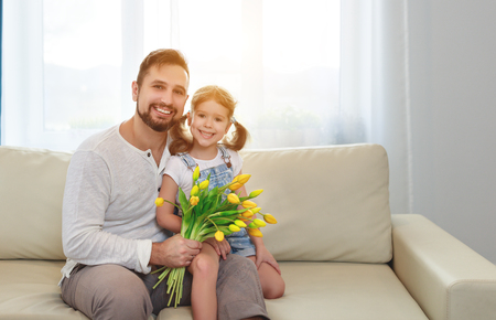 father and child daughter with a bouquet of flowers at home