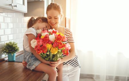 feliz día de la madre! hija hija felicita a la madre y regala un ramo de flores a tulipanes Foto de archivo - 97650064
