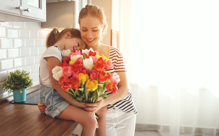 happy mothers day! child daughter congratulates mother and gives a bouquet of flowers to tulips  Stock Photo