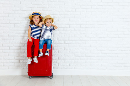 happy laughing children boy and girl with suitcase going on a trip Archivio Fotografico