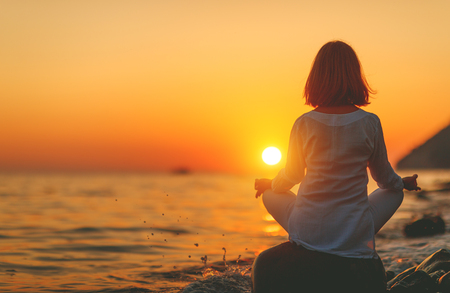 woman practices yoga and meditates in the lotus position on sunset beach  Stock fotó