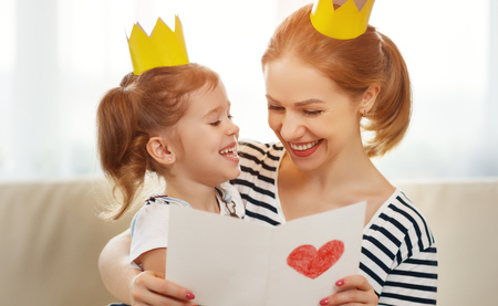 happy mothers day! mother and child daughter in crowns  and with postcard