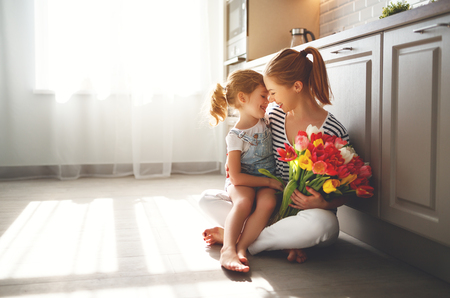 happy mothers day! child daughter congratulates mother and gives a bouquet of flowers to tulips  Stok Fotoğraf