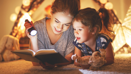 reading and family games in   tent. mother and child daughter reading book and flashlight before going to bed  Stock Photo