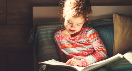 girl child reads book in bed before bedtime
