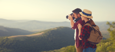happy couple tourist with photo camera at top of mountain at sunset outdoors during a hike in summer