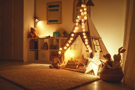 interior of a childrens playroom with a tent, lamps and toys in dark