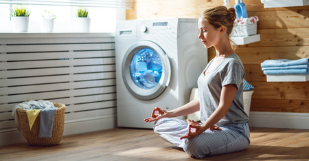 tired woman housewife in stress meditates in a lotus yoga pose in laundry