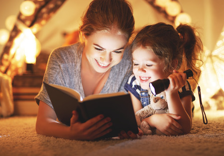 reading and family games in   tent. mother and child daughter reading book and flashlight before going to bed  Banco de Imagens