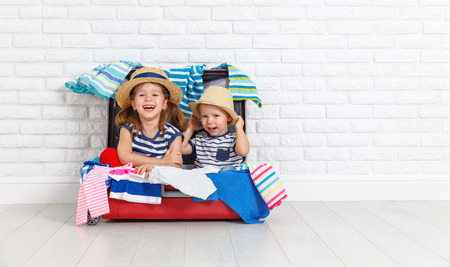 happy laughing children boy and girl with suitcase going on a trip  Stock Photo