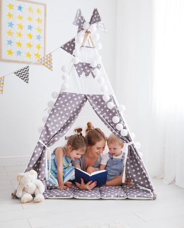 family mother reading to children book in tent in playroom at home