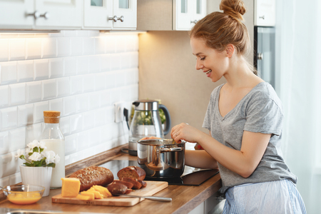 young woman in pajamas prepares breakfast in the morning Banco de Imagens