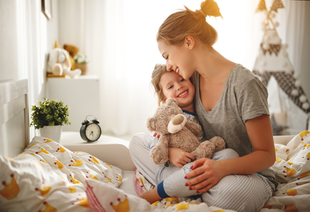 morning awakening. mother wakes her daughter in bed in morning Banco de Imagens - 100274325