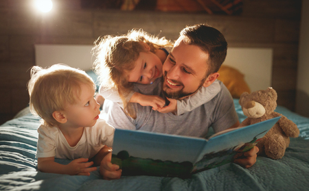 evening family reading. father reads children a book before going to bed