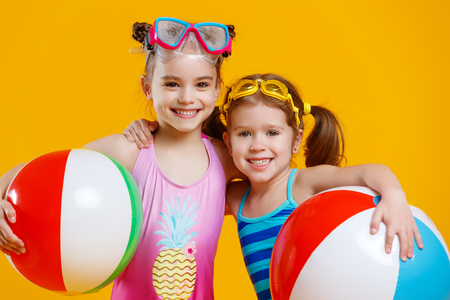 funny funny happy children in bathing suits and swimming glasses prepare for beach rest on colored background