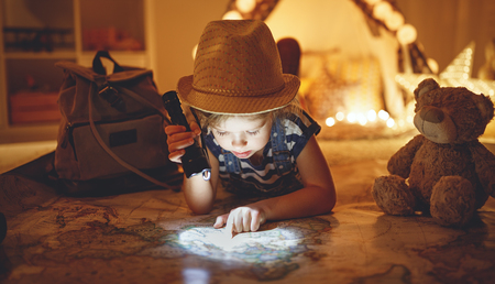 funny happy child girl tourist with flashlight and world map and backpack   Stockfoto