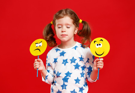 concept of childrens emotions. child girl chooses between a sad and joyful smile on  colored red background