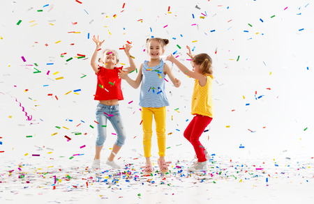 happy children on holidays have fun and  jumping in multicolored confetti on white background Archivio Fotografico