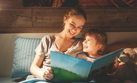 madre e figlia del bambino che leggono il libro a letto prima di andare a dormire Archivio Fotografico