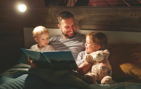 Avond familie lezen. vader leest kinderen een boek voordat ze naar bed gaan Stockfoto - 100277151