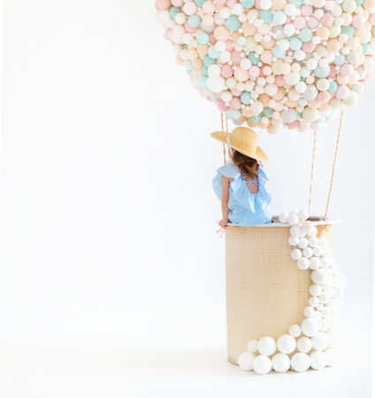 cute charming child girl in a fairy magic hot air balloon