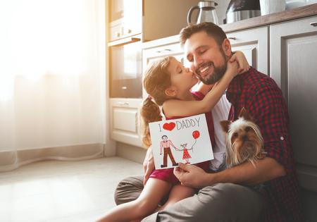 Dia del padre. Hija de familia feliz dando a papá una tarjeta de felicitación de vacaciones Foto de archivo - 101019712