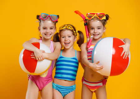 divertido niños divertidos felices saltando en traje de baño y gafas de sol saltando en el fondo de color Foto de archivo