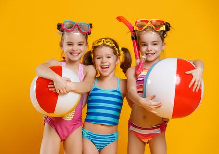 Lustige lustige glückliche Kinder springen in Badeanzug und Schwimmbad auf farbigem Hintergrund fliegen Standard-Bild