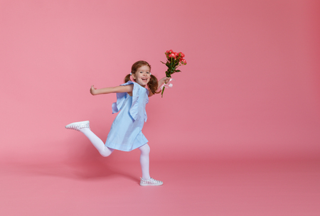 funny child girl runs and jumps with bouquet of flowers on a colored background
