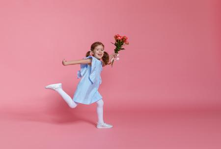 Lustiges Kind Mädchen läuft und springt mit Blumenstrauß auf einem farbigen Hintergrund
